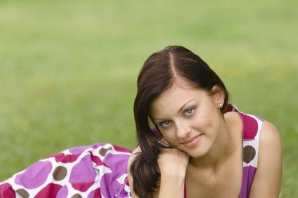 Bei Verdacht auf Scheidenpilz zum Arzt; junge Mädchen; junges Mädchen im Sommerkleid liegt auf einer Wiese