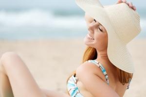Scheidenpilz ade – dank Antipilzmittel den Urlaub wieder genießen; lachende Frau im Bikini am Strand