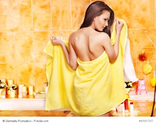Übertriebene Intimhygiene kann eine Ursache für Scheidenpilz sein; Frau steht in ein Handtucch gewickelt im Bad